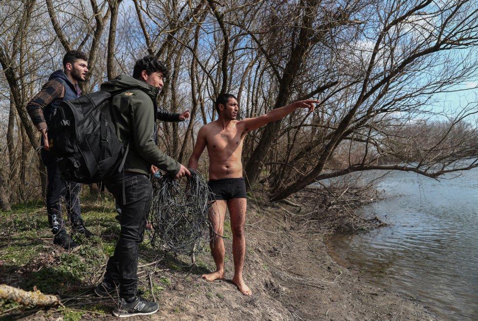 إيماءات مهاجر قبل عبور نهر إفروس للوصول إلى الجانب اليوناني من الحدود التركية اليونانية ، في أدرنة (تركيا) ، في 1 مارس.
