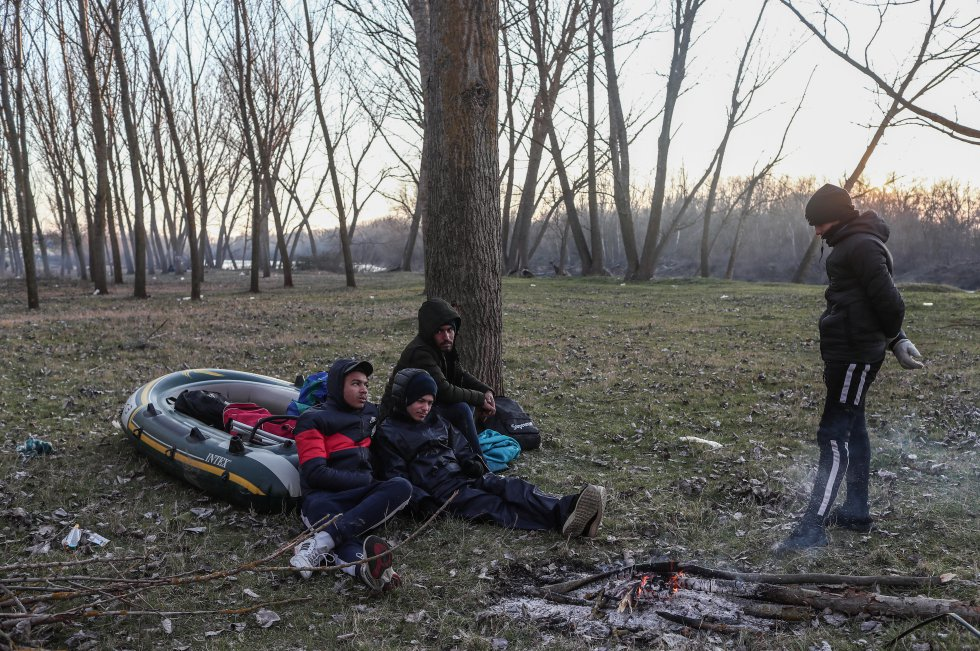 """مجموعة من المهاجرين يستريحون مع قاربهم أثناء انتظارهم لعبور نهر إفروس في تركيا في الأول من مارس.  يقول ناصر أبو سامي ، سوري آخر ، يأخذهم: """"إنهم لا يسمحون لنا بالعودة. يأتون بحافلات خاصة ويأخذوننا من هذه الخطوة إلى أخرى. ومن هناك إلى آخر. ثم يعيدوننا. يلعبون معنا ، لا شيء أكثر من ذلك"""". يومين مع عائلته في المنطقة."""