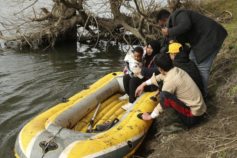 عائلة تستخدم قاربًا لعبور نهر إفروس في الأول من مارس.  تقوم الحافلات ، التي لا يعرف أحد من قام باستئجارها ، بتوزيع المهاجرين في مجموعات صغيرة على طول حوالي 25 كيلومترًا من الحدود.