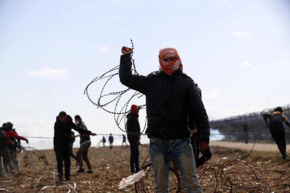 مجموعة من اللاجئين يحاولون قطع السياج على الحدود التركية اليونانية في 2 مارس.  أكدت المنظمة الدولية للهجرة مقتل أكثر من 60 مهاجراً هذا العام في شرق البحر المتوسط.  في الأيام الأخيرة ، واجهت اليونان انتعاشًا جديدًا في الوافدين بسبب تصاعد التوترات في شمال غرب سوريا.