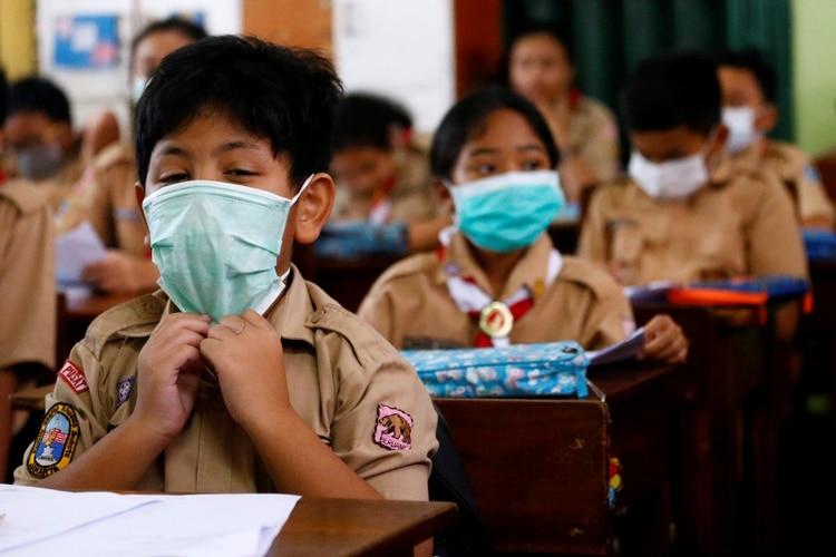 يرتدي الطلاب أقنعة في جاكرتا بإندونيسيا (رويترز / أجينغ دينار أولفيانا)