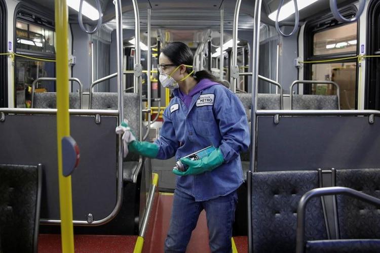 عامل خدمة صيانة المركبات Thiphavanh 'Loui' Thepvongsa ينظف حافلة خارج الخدمة مع مطهر أثناء التنظيف الروتيني في King County Metro Atlantic و Central Base في سياتل ، واشنطن (REUTERS / Jason Redmond)