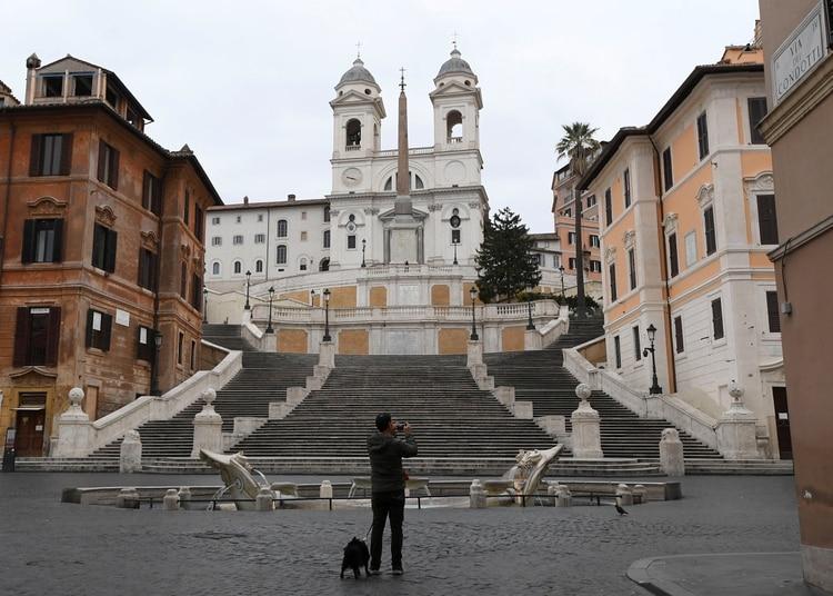 رجل يلتقط صورة للسائح عبر كوندوتي مع عدم وجود أشخاص حوله حيث تواصل الحكومة الإيطالية إجراءات الحركة التقييدية لمكافحة تفشي الفيروس التاجي في روما ، إيطاليا في 14 مارس 2020 (رويترز / ألبرتو لينجريا)