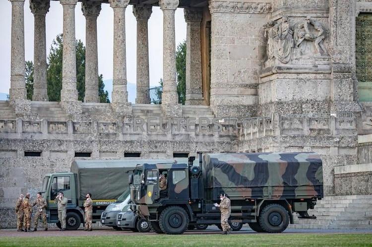 الجنود الإيطاليون في مقبرة بيرغامو بعد نشر الجيش لنقل التوابيت من المقبرة إلى المقاطعات المجاورة ، بعد أن طغت المقبرة في 18 مارس 2020 من اندلاع فيروس كورونا (COVID-19) ، في إيطاليا (Sergio Agazzi. Photogram via REUTERS)