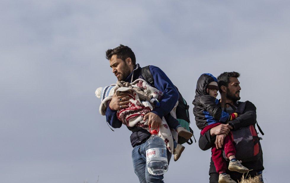 يعبر مهاجران مع أطفالهما بين أذرعهم مدينة أدرنة (تركيا) ، في رحلتهم إلى اليونان ، في 3 مارس.