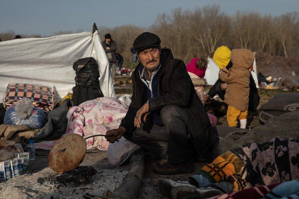 رجل يحمص الخبز على نار ، في معسكر مؤقت بالقرب من نهر إفروس (تركيا) ، في 3 مارس.