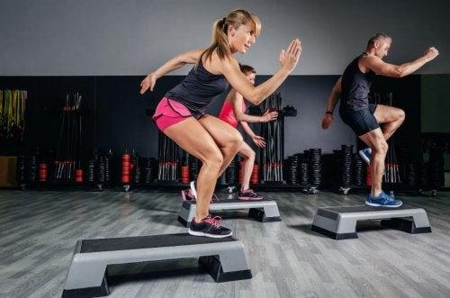 الناس في صالة الألعاب الرياضية يقومون بتمارين الأيروبيك.