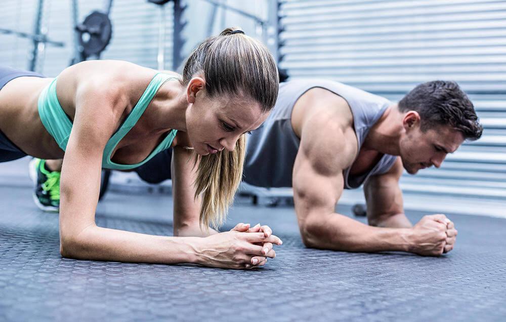 زوجان من الرياضيين يقومان بلوح في صالة الألعاب الرياضية