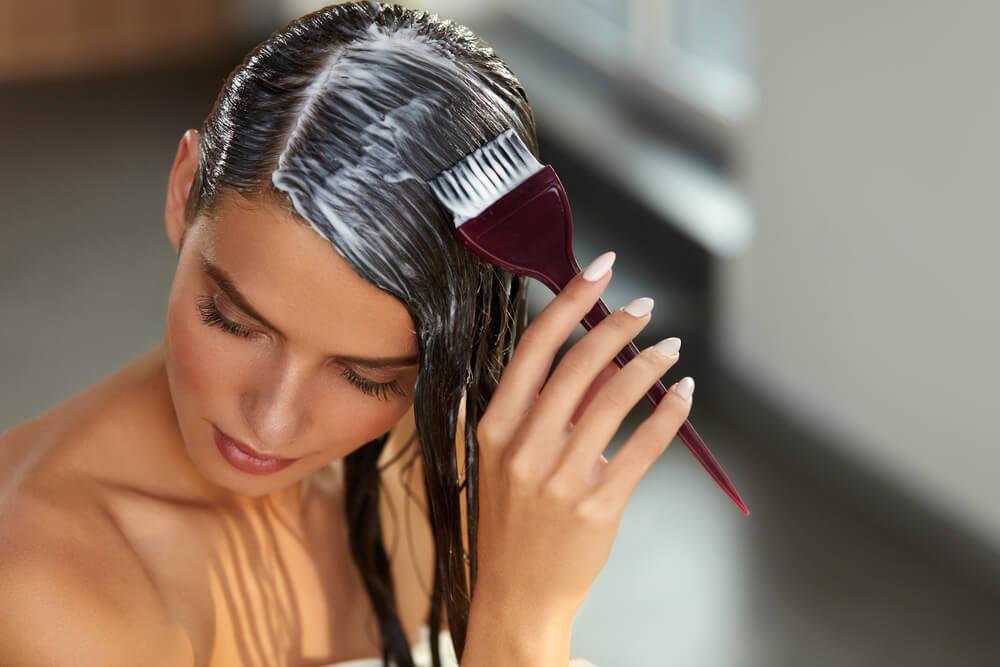 امرأة تضع قناعًا على شعرها بمساعدة مشط على شكل فرشاة.