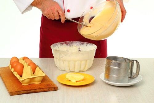طهي كريمة الخفق في وعاء مع مكونات أخرى لتحضيرها على الطاولة.