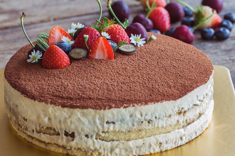 كعكة تيراميسو محلية الصنع مع الفراولة والكاكاو في الأعلى.